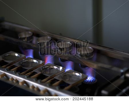 Cement melting under high pressure and temperature. Four cups prepared for melting a cement material on a blurred industrial background. Dangerous manufacturing equipment. Copy space.