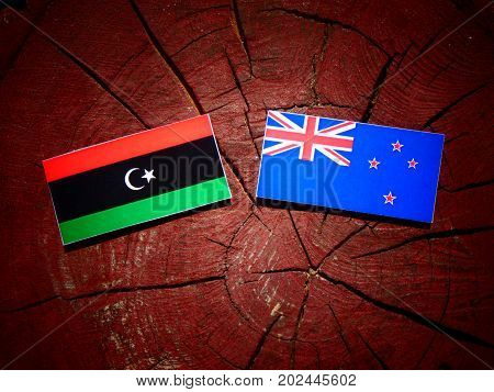 Libyan Flag With New Zealand Flag On A Tree Stump Isolated
