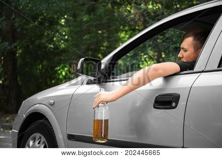 A drunk, boozed man driving a big gray car holding a bottle of beer. An alcoholic driving and drinking on a blurred natural background. Accident on a road, illegal driving and alcohol abuse concept.