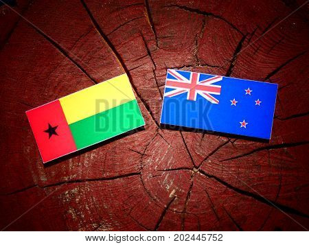 Guinea Bissau Flag With New Zealand Flag On A Tree Stump Isolated