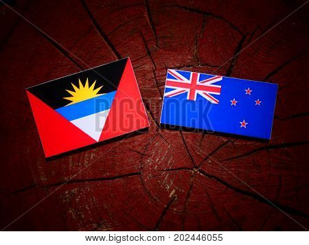 Antigua And Barbuda Flag With New Zealand Flag On A Tree Stump Isolated