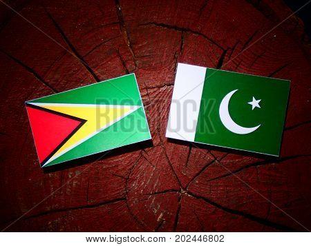 Guyana Flag With Pakistan Flag On A Tree Stump Isolated