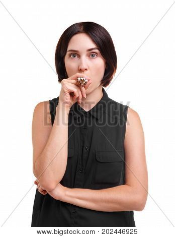 Portrait of a female nicotine addict smoking many cigarettes isolated on a white background. A beautiful, funny brunette girl with a stylish haircut in a black blouse, holding cigarettes.