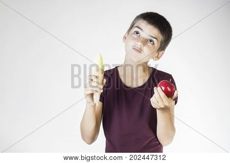 Portrait happy smiling boy choosing fruits and sweets. Healthy versus unhealthy food. Healthy vs unhealthy eating teenager choosing between cake or an apple.
