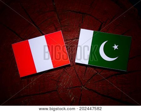 Peruvian Flag With Pakistan Flag On A Tree Stump Isolated