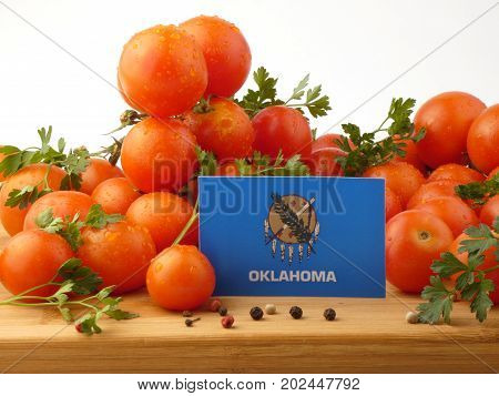 Oklahoma Flag On A Wooden Panel With Tomatoes Isolated On A White Background
