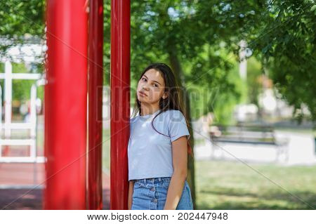 A close-up portrait of a tender young girl wearing a gray crop top and denim skirt on a blurred natural background. A beautiful adolescence lady posing outdoors. Youth, beauty, outdoors concept.