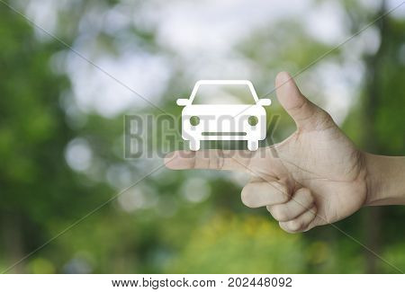 Car flat icon on finger over blur green tree background Business service car concept