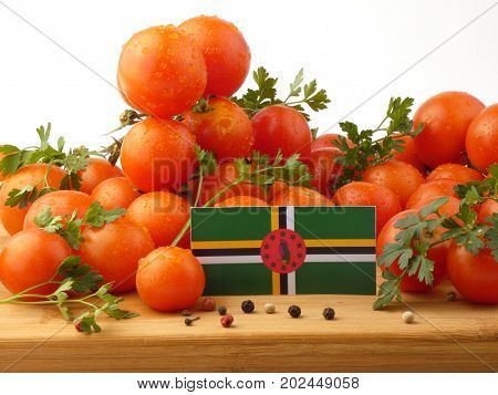 Dominica Flag On A Wooden Panel With Tomatoes Isolated On A White Background