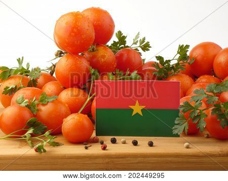 Burkina Faso Flag On A Wooden Panel With Tomatoes Isolated On A White Background