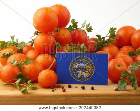 Nebraska Flag On A Wooden Panel With Tomatoes Isolated On A White Background