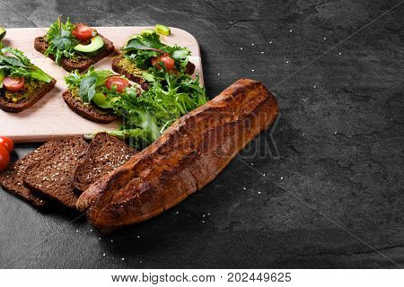 close-up picture of rustic, freshly baked, crunchy and crispy sliced black baguette bread on a black table background. Bread next to a cutting desk with vegetable sandwiches and green arugula leaves.