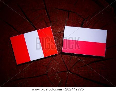 Peruvian Flag With Polish Flag On A Tree Stump Isolated