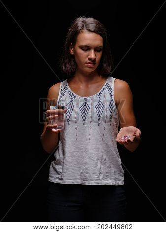 A tanned girl holding colorful tablets and a glass of water in her hands on a black background. A young woman in a white blouse with a heap of painkillers in a hand. Medicine, suicide concept.