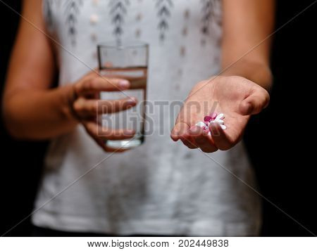 A close-up of a female holding pink tablets on a black background. A young woman in a white blouse with a heap of painkillers and a glass of water in her hands. Medicine, healthcare concept.