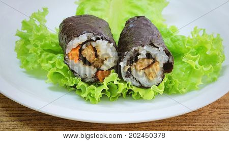 Japanese Cuisine Traditional Vagetarian Japanese Rice Maki Sushi Roll Stuff with Tofu and Carrot Wrapped in Nori Seaweed Served on Green Oak.