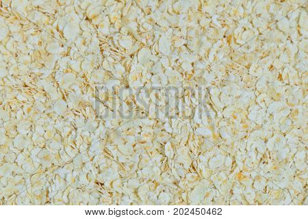 Cuisine and Food Close Up of Uncooked Rolled Oat or Oat Flakes Textured Background. Nutrient Rich Food with Lower Blood Cholesterol.