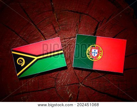 Vanuatu Flag With Portuguese Flag On A Tree Stump Isolated