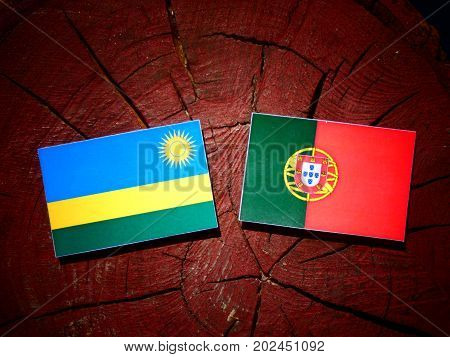 Rwanda Flag With Portuguese Flag On A Tree Stump Isolated