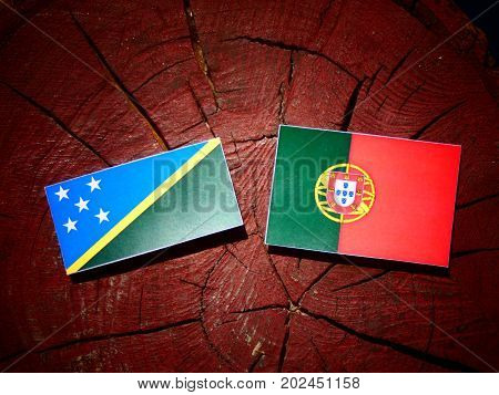 Solomon Islands Flag With Portuguese Flag On A Tree Stump Isolated