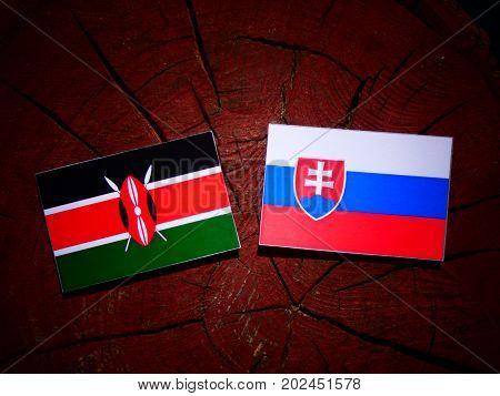 Kenyan Flag With Slovakian Flag On A Tree Stump Isolated