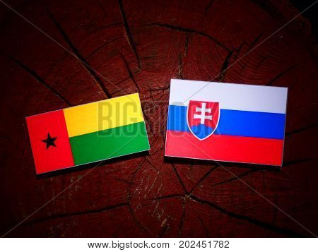 Guinea Bissau Flag With Slovakian Flag On A Tree Stump Isolated