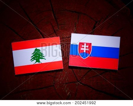 Lebanese Flag With Slovakian Flag On A Tree Stump Isolated