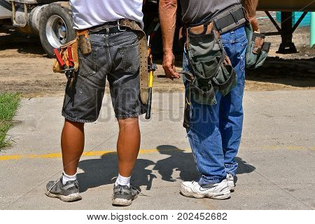 A pair of unidentified  wood carpenters stand with work tools attached to their belts