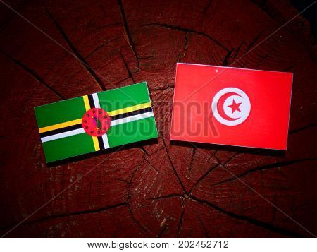 Dominica Flag With Tunisian Flag On A Tree Stump Isolated