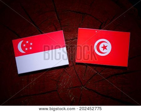 Singaporean Flag With Tunisian Flag On A Tree Stump Isolated