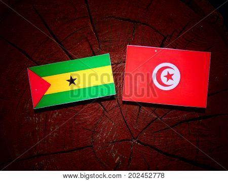 Sao Tome And Principe Flag With Tunisian Flag On A Tree Stump Isolated