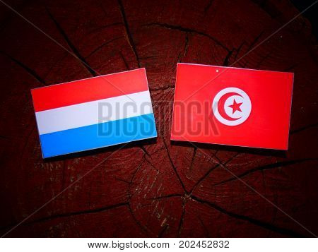 Luxembourg Flag With Tunisian Flag On A Tree Stump Isolated