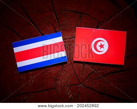 Costa Rican Flag With Tunisian Flag On A Tree Stump Isolated