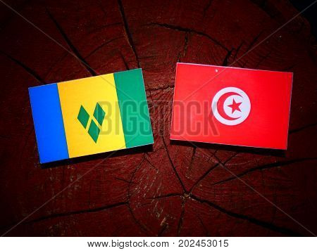 Saint Vincent And The Grenadines Flag With Tunisian Flag On A Tree Stump Isolated