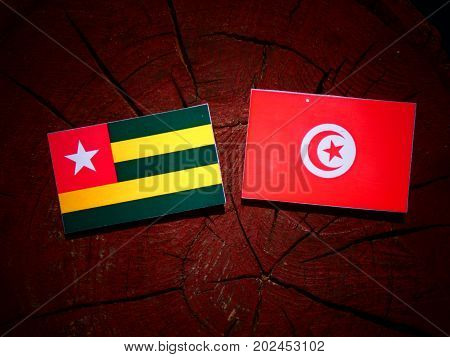 Togolese Flag With Tunisian Flag On A Tree Stump Isolated