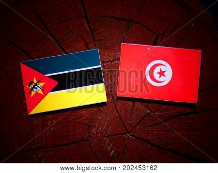 Mozambique Flag With Tunisian Flag On A Tree Stump Isolated