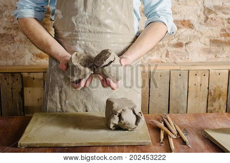 potter workshop ceramics art concept - standing young brunette man dressed in an apron male hands knead the fireclay a ceramist with raw materials on wooden table with sculpting tools set