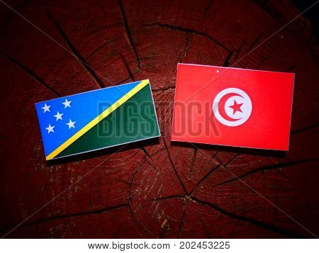 Solomon Islands Flag With Tunisian Flag On A Tree Stump Isolated