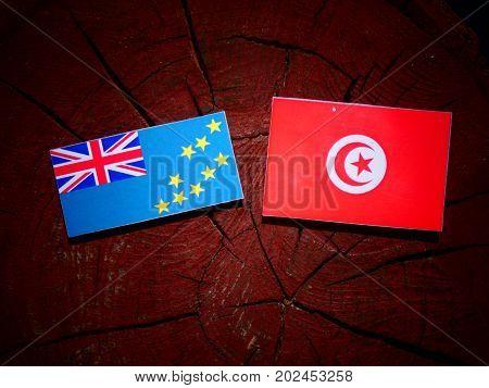 Tuvalu Flag With Tunisian Flag On A Tree Stump Isolated