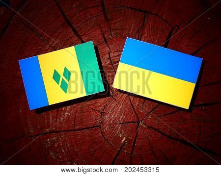 Saint Vincent And The Grenadines Flag With Ukrainian Flag On A Tree Stump Isolated
