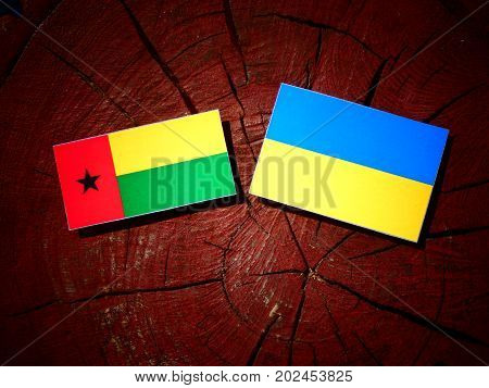 Guinea Bissau Flag With Ukrainian Flag On A Tree Stump Isolated