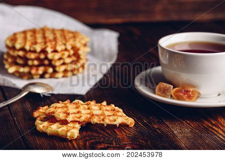 Breakfast with White Cup of Tea with Waffles Stack on Napkin and Pieces of Waffle on Wooden Surface.