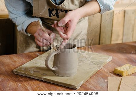 potter workshop ceramics art concept - ceramist holding cup and carefully examines the product young male master dressed in a stained clay apron craftsman's hands holding unbaked jug
