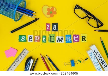 September 28th. Day 28 of month, Back to school concept. Calendar on teacher or student workplace background with school supplies on yellow table. Autumn time.