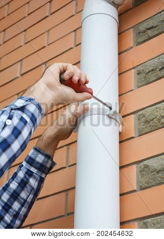 Worker Installing rain gutter downspout pipe. Contractor hands repair rain gutter downspout pipe with screwdriver. Guttering Rain Chain Plastic Guttering & Drainage. Guttering Down pipe Fittings