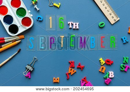 September 16th. Day 16 of month, Back to school concept. Calendar on teacher or student workplace background with school supplies on blue table. Autumn time.