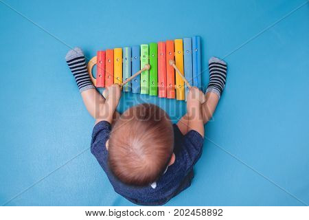 Bird eye view of Cute little Asian 18 months / 1 year old baby boy child hold sticks & plays a musical instrument colorful wooden toy xylophone Educational toy for kids and toddlers concept