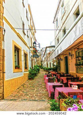 Tossa de Mar, Spain - September 14, 2015: The street cafe at old town Tossa de Mar in Costa Brava, Catalonia, Spain on September 14, 2015