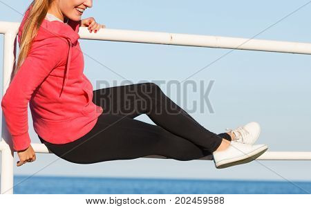Woman Sitting On Handrail By The Sea