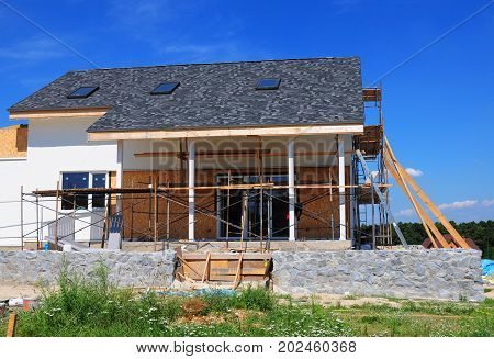 Roofing Construction. House Construction with asphalt shingles roof skylights terrace patio. Attic skylight.